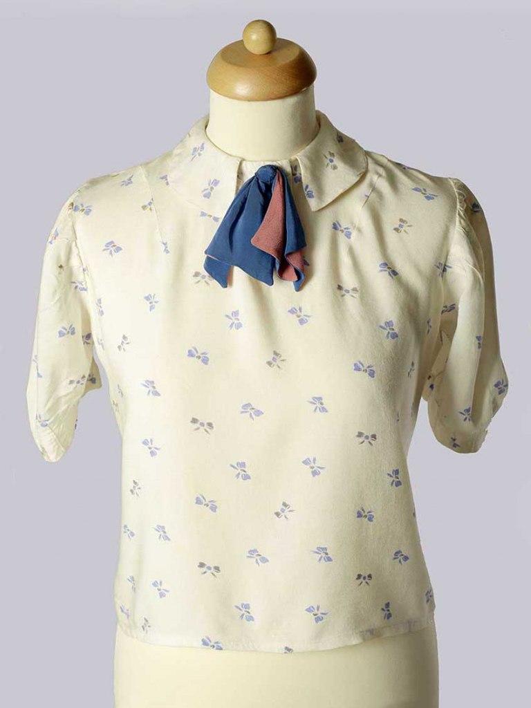 <p>Bavlněná halena s hedvábnou mašlí u krku, kol. poloviny 20. století.</p>