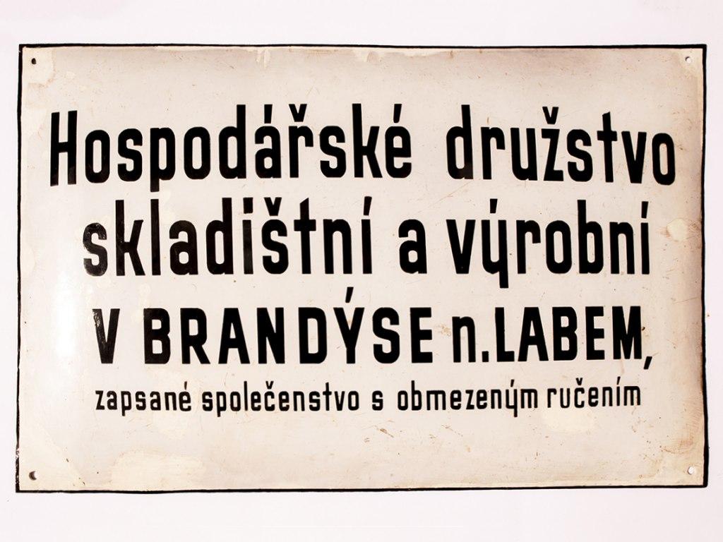 <p>Vývěsní štít Hospodářského družstva skladištního a výrobního vBrandýse n. L., 20. – 40. léta 20. století.</p>